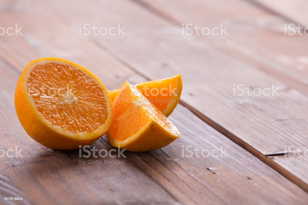 Sliced orange on brown wooden background stock photo