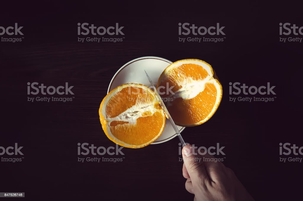 sliced orange particles to a steel knife blades stock photo