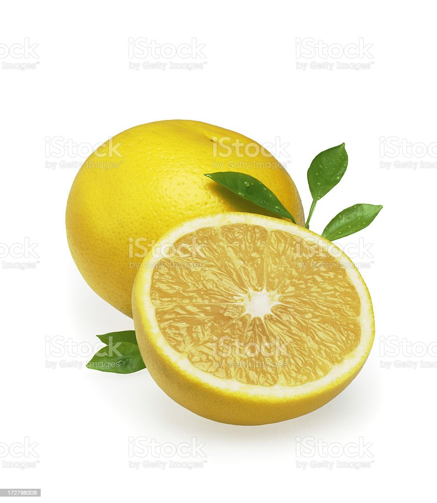 Sliced orange with leaves in front of a whole orange stock photo