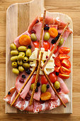 Sliced pancetta and salami with olives, cheese, cherry tomato