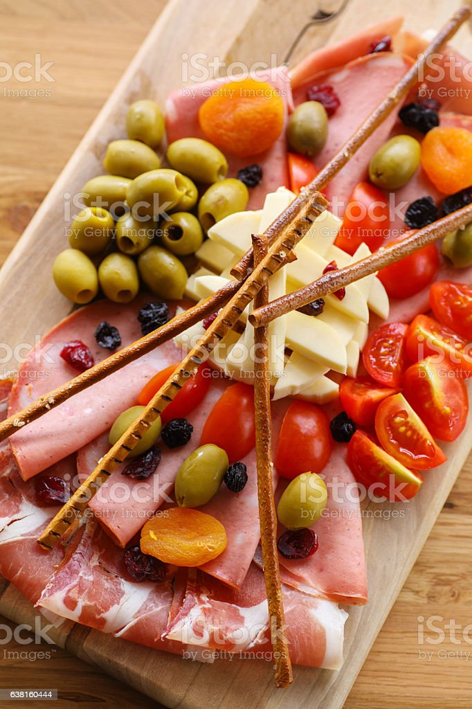 Sliced pancetta and salami with olives, cheese, cherry tomato stock photo