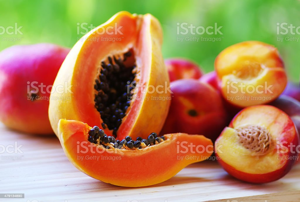 sliced papaya and mangoes fruits on the table. stock photo