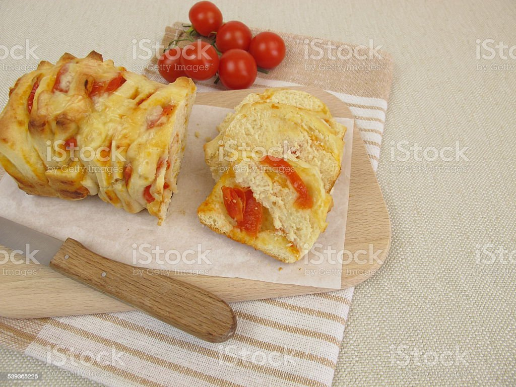 Sliced pizza pull-apart bread with tomatoes and cheese stock photo