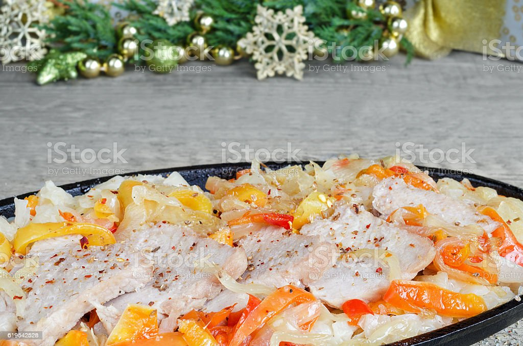Sliced pork with vegetables in a frying pan,on  wooden stock photo