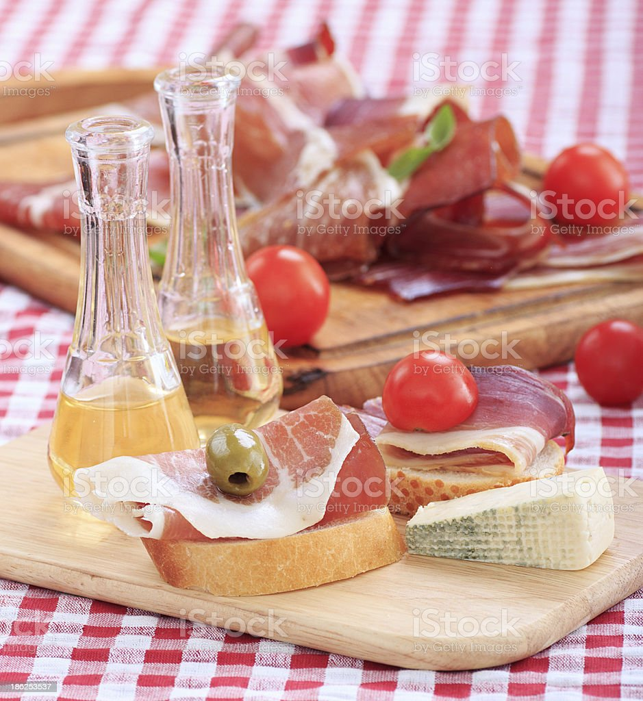 sliced prosciutto with olive cheese Cherry tomato and schnapps. royalty-free stock photo