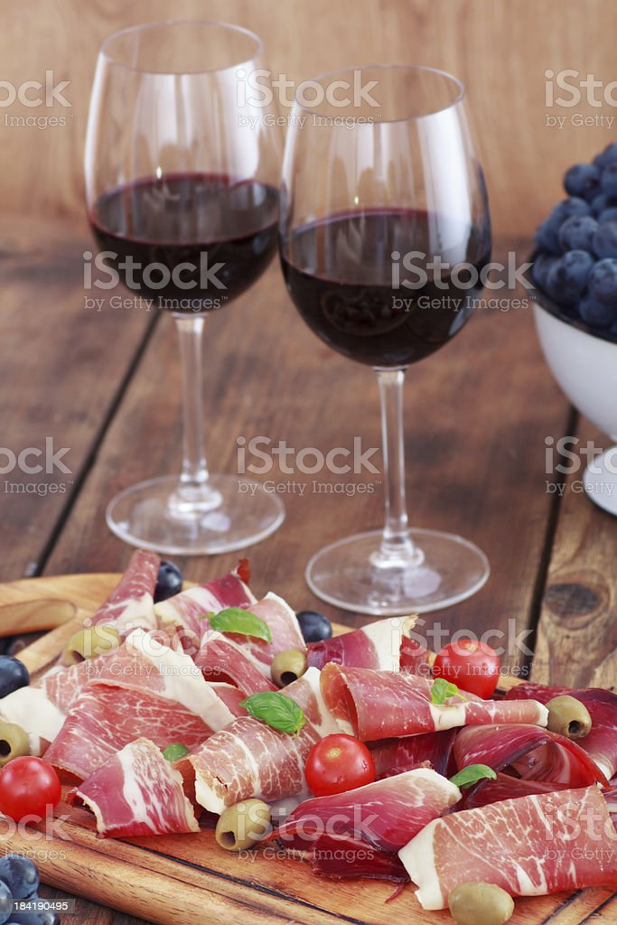 sliced prosciutto with red wine and olives royalty-free stock photo