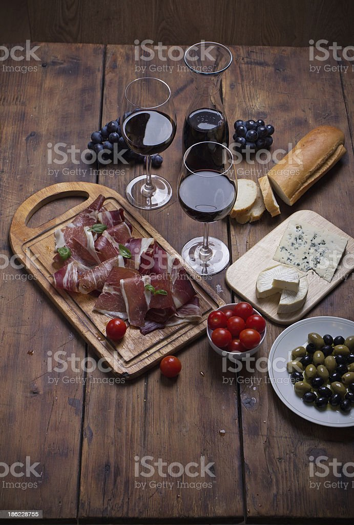 sliced prosciutto with red wine cheese and olives royalty-free stock photo
