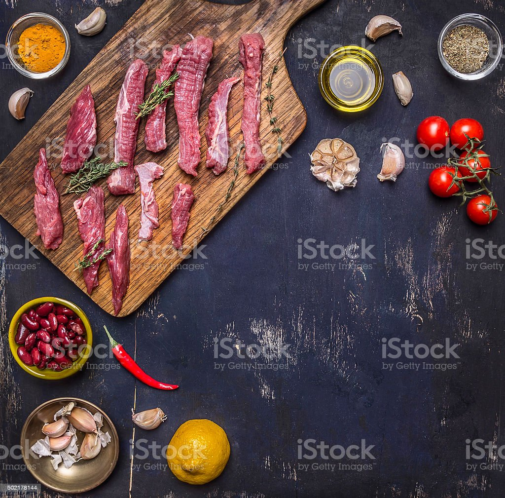 sliced raw beef lemon, tomatoes spices wooden rustic background top stock photo