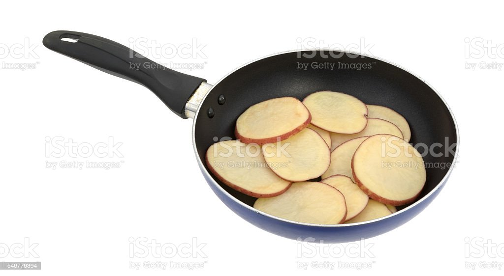 Sliced red potatoes in an old skillet side view. stock photo