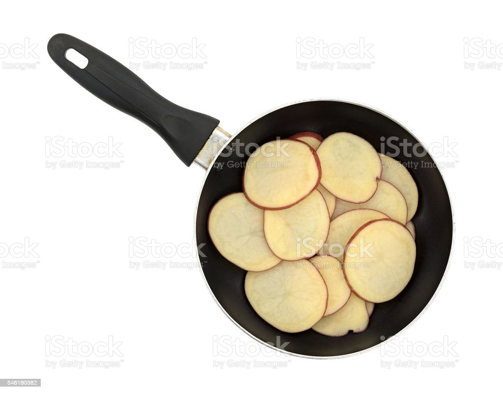 Sliced red potatoes in an old skillet top view. stock photo