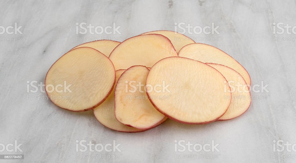 Sliced red potatoes on a marble cutting board. stock photo