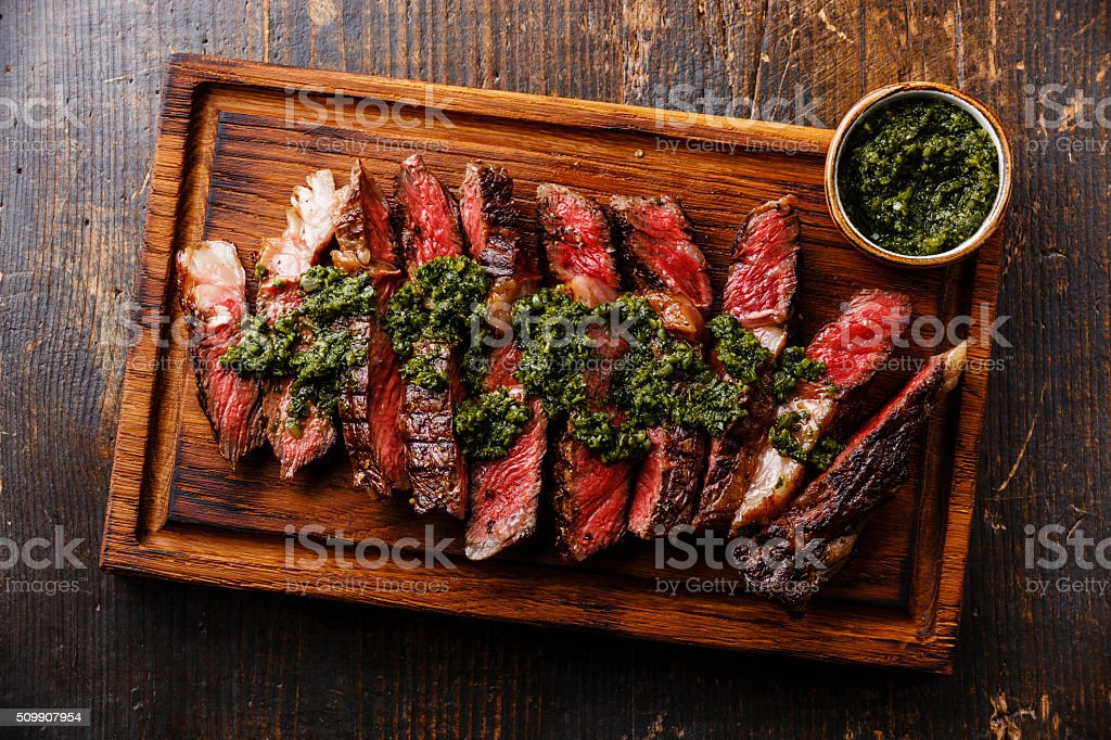 Sliced Ribeye steak with chimichurri sauce stock photo