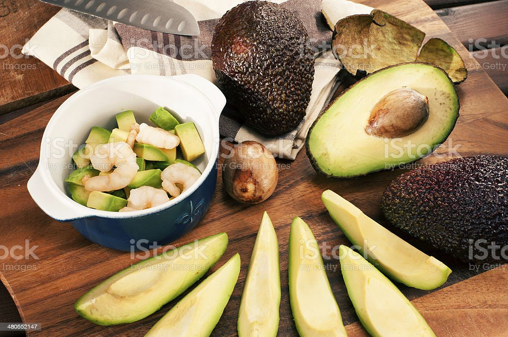 Sliced ripe avocado with shrimps in ceramic cocotte royalty-free stock photo