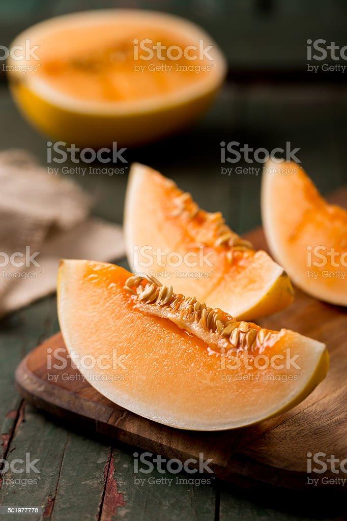 sliced ripe melon on a cutting board stock photo