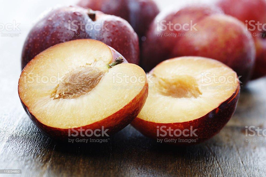 sliced ripe plumbs on dark oak stock photo