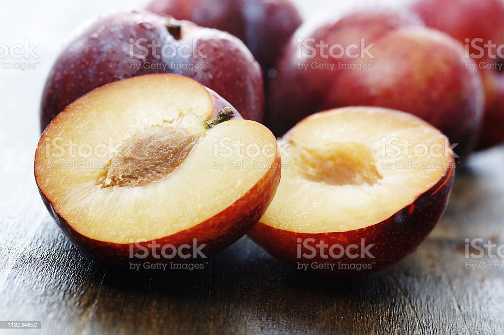 sliced ripe plumbs on dark oak stock photo