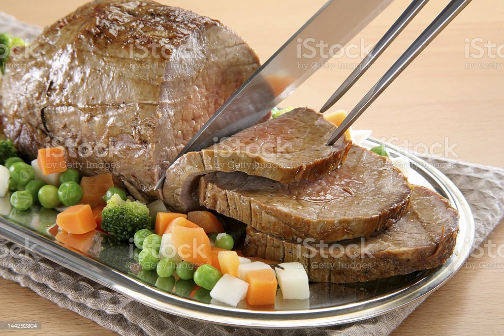 Sliced roast beef with broccoli, carrots and peas stock photo