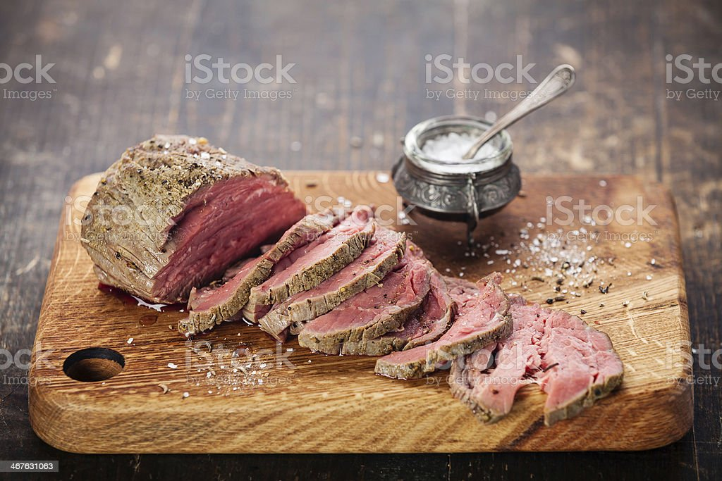 Sliced roast beef with salt in pot on wooden chopping board stock photo