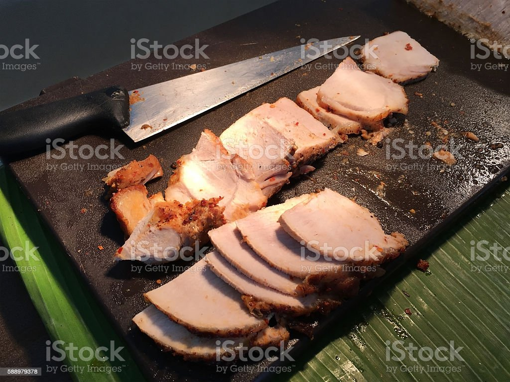 Sliced roast pork on chopping wood block In the dining stock photo
