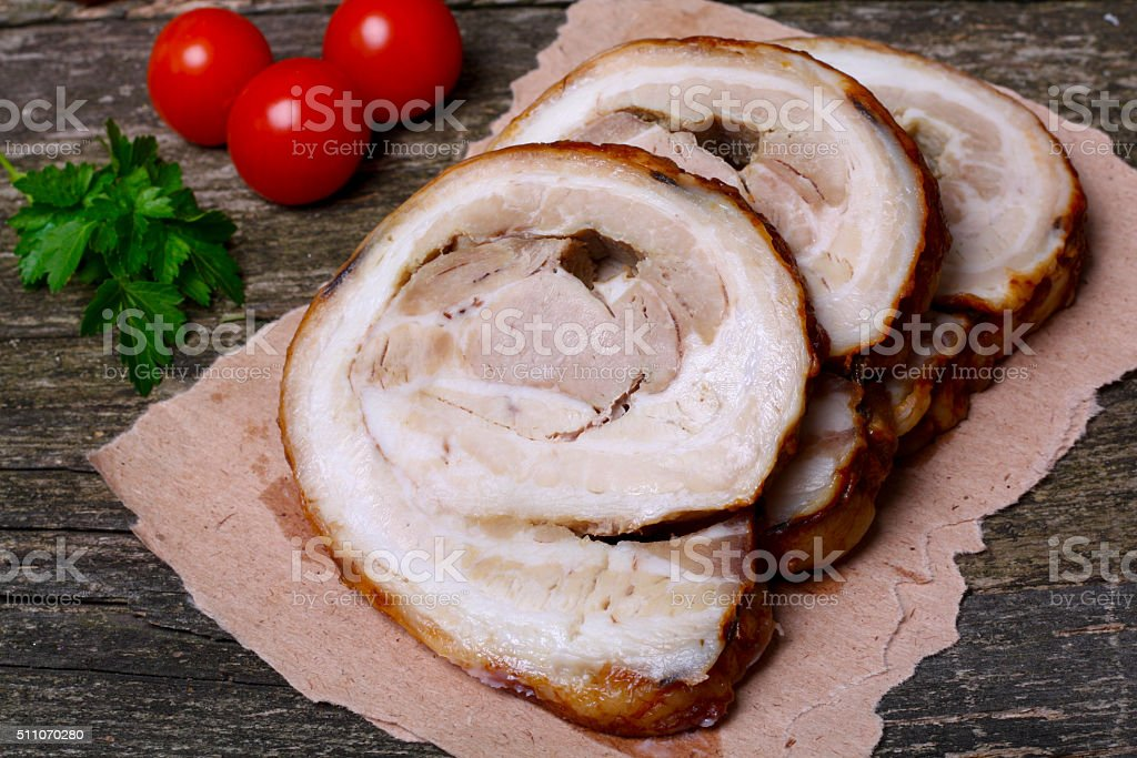 Sliced roasted roll pork loin with spices and fresh vegetables stock photo