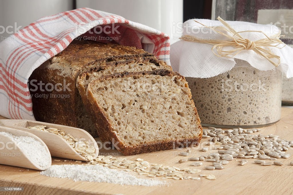 Sliced rye bread coveted in cloth next to oats and jar stock photo