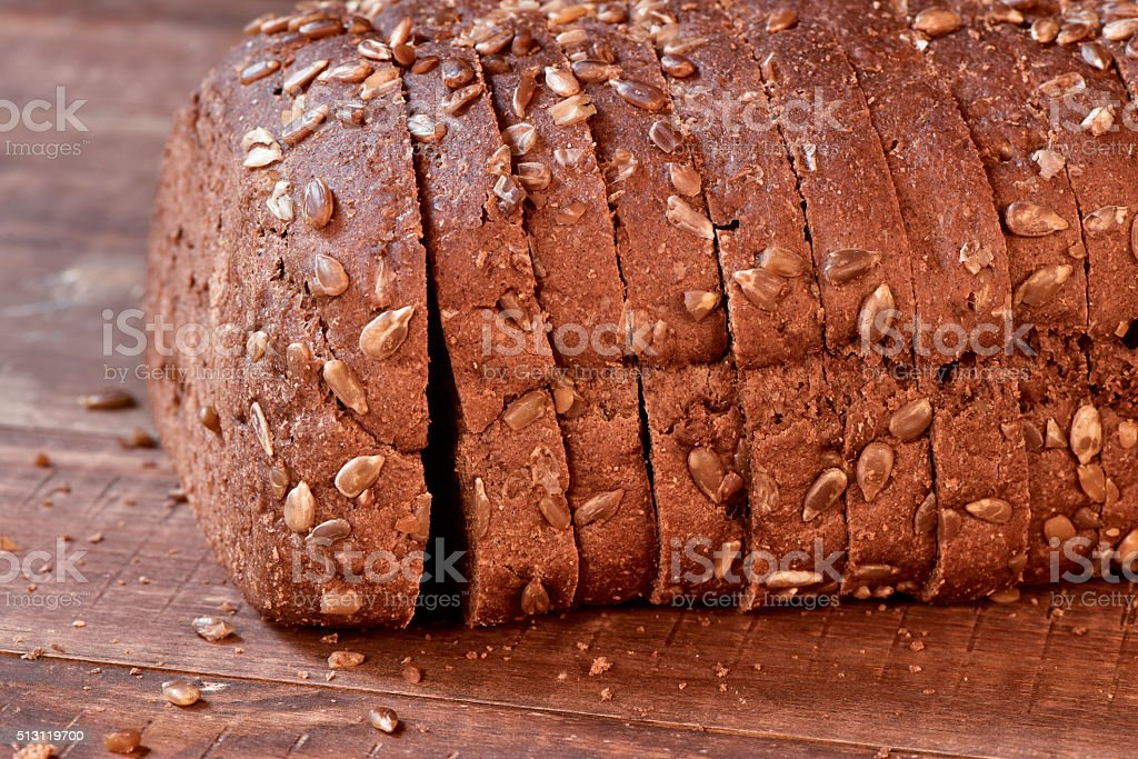 sliced rye bread on a wooden surface stock photo