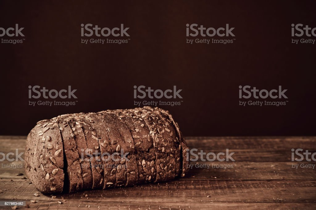 sliced rye bread on a wooden surface, sepia toned stock photo