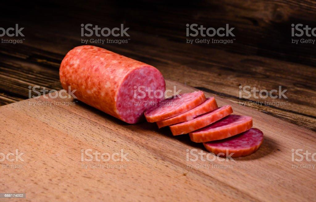 Sliced salami sausage on cutting board stock photo