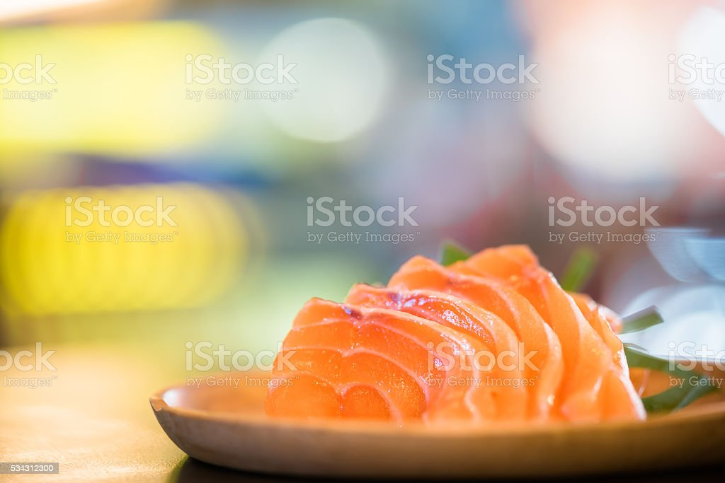 Sliced salmon sashimi served on wooden platter, bokeh background stock photo
