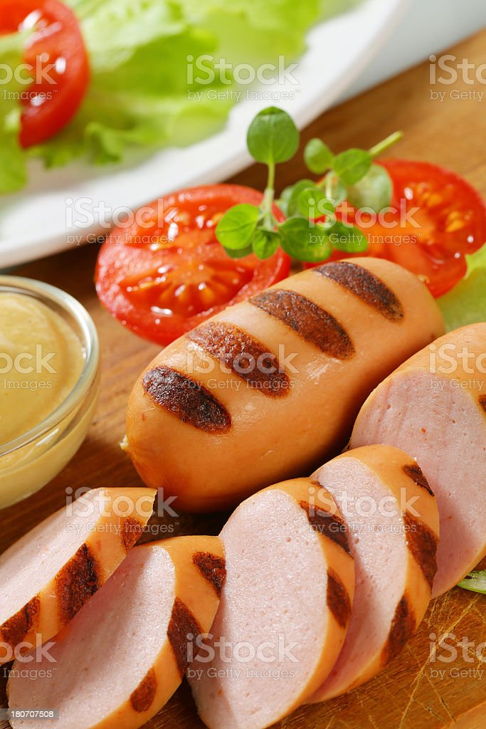 sliced sausage, mustard and vegetable garnish royalty-free stock photo