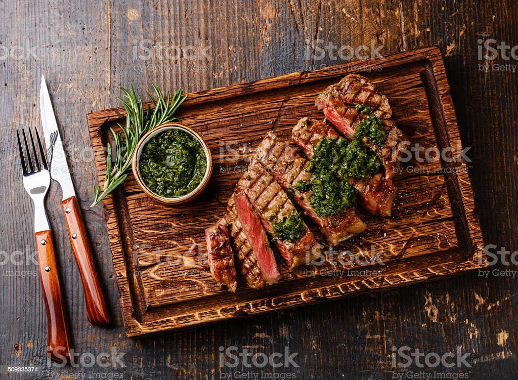Sliced Sirloin steak with chimichurri sauce stock photo