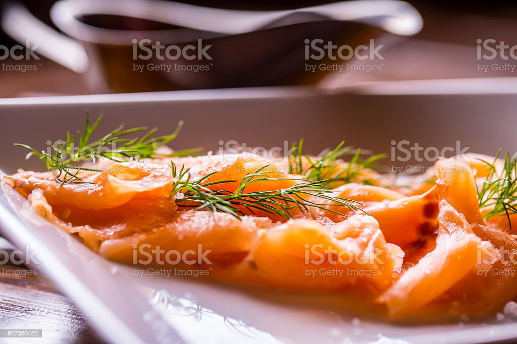 Sliced smoked salmon with dressing and herb decoration. stock photo