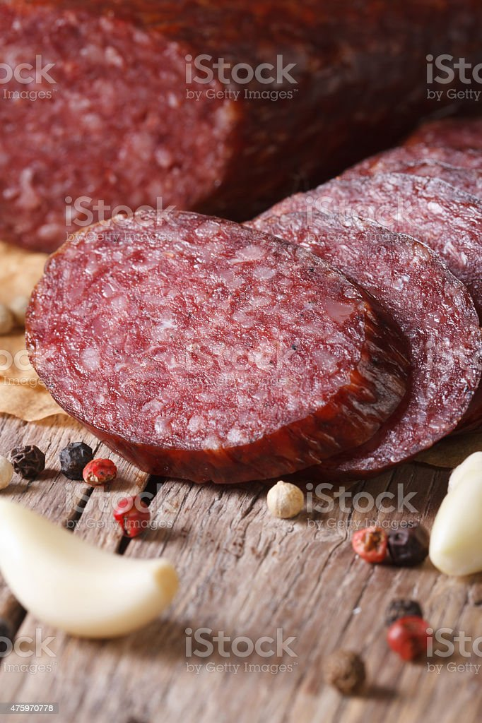 Sliced smoked sausage with spices vertical macro stock photo