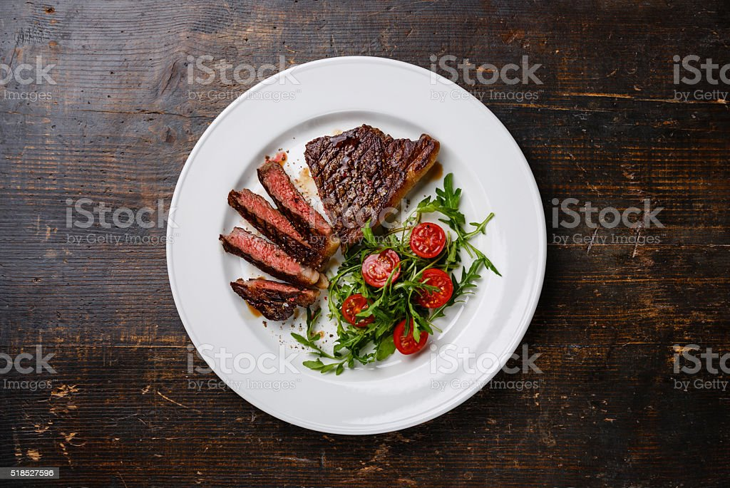 Sliced steak Striploin and salad with tomatoes and arugula stock photo