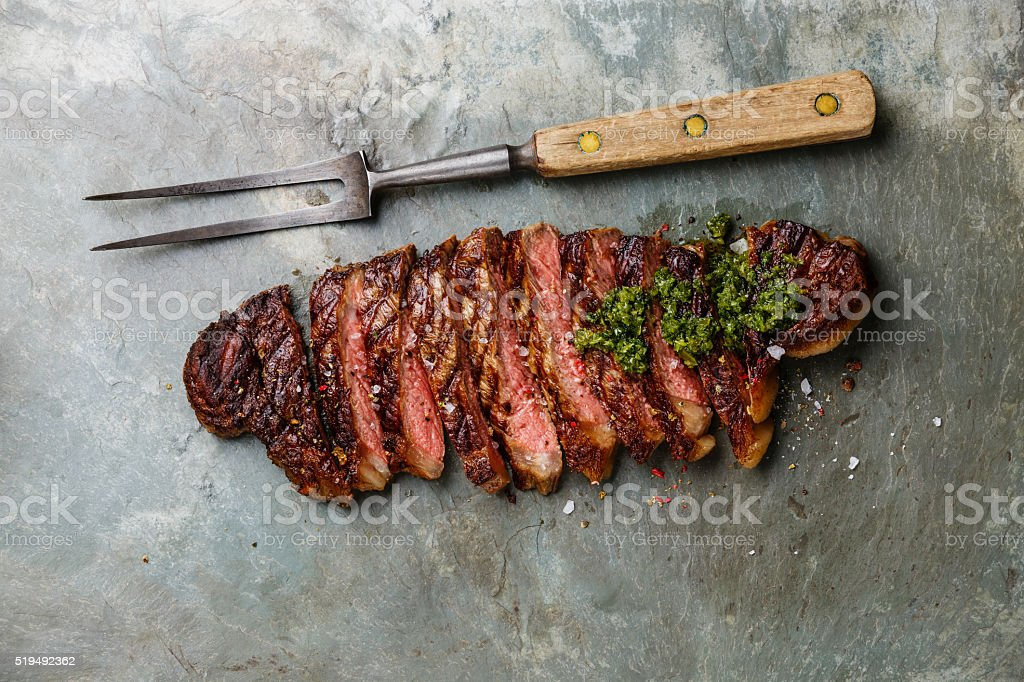 Sliced steak with chimichurri sauce and meat fork stock photo