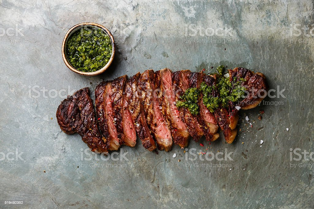Sliced steak with chimichurri sauce stock photo