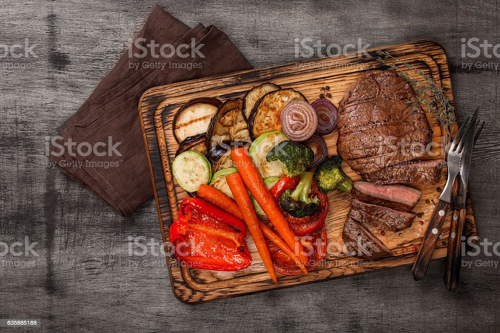 Sliced steak with grilled vegetables and sauce on wooden board stock photo