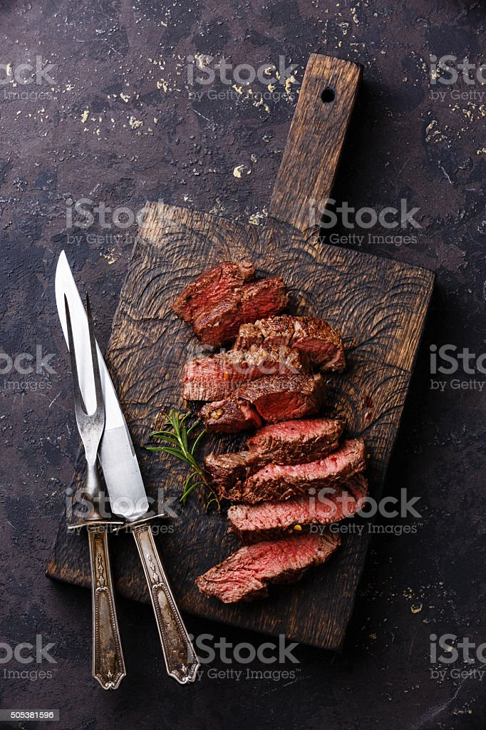 Sliced steak with knife and fork for meat stock photo