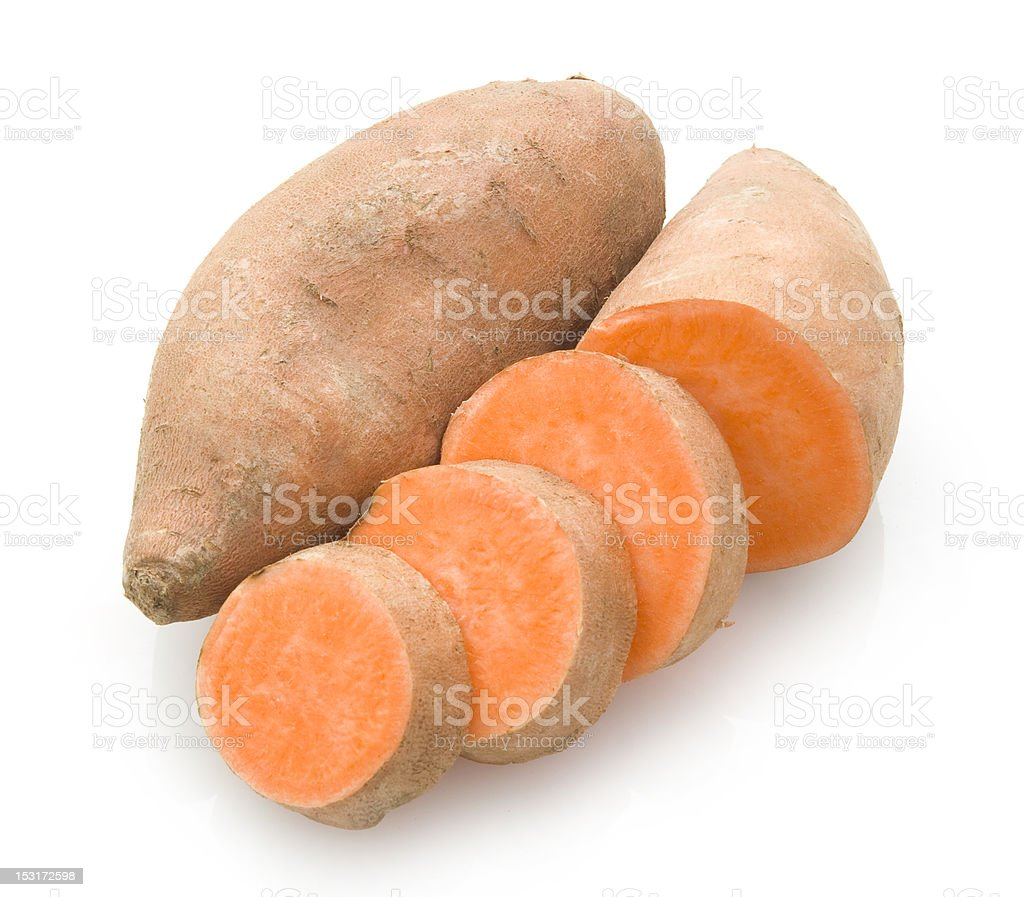 Sliced sweet potato next to a whole potato stock photo