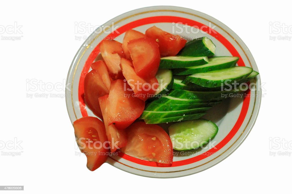 Sliced tomatoes and cocumbers on the round plate isolated stock photo