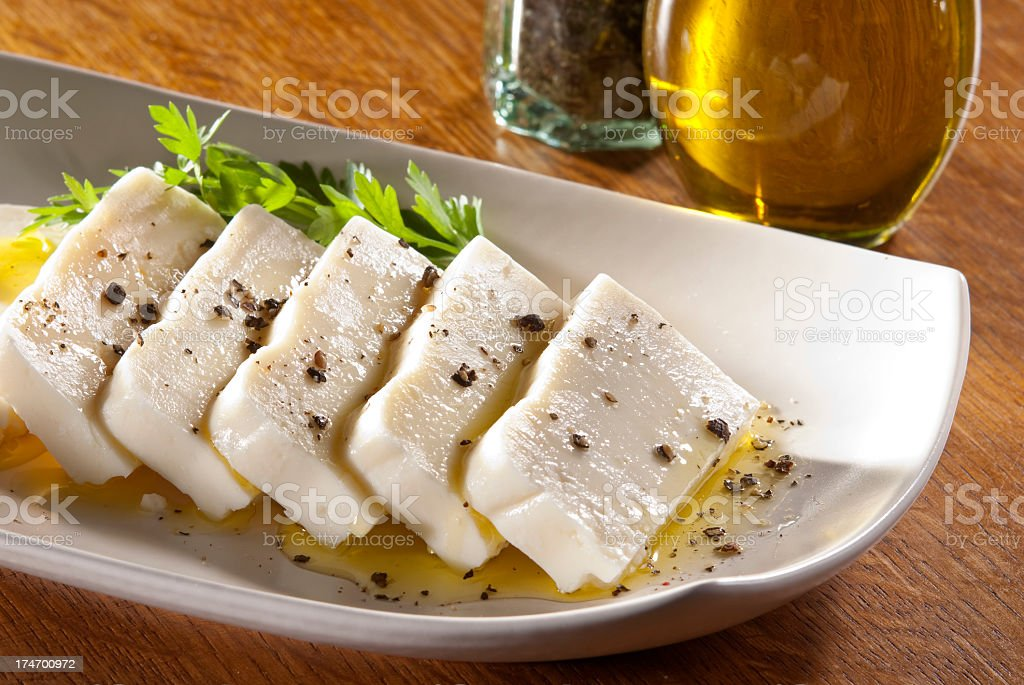 Sliced Turkish feta cheese with olive oil and herb garnish royalty-free stock photo