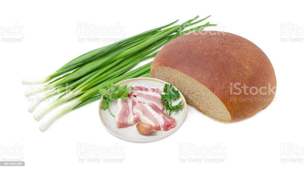 Sliced uncooked bacon, round wheat and rye bread and greens stock photo
