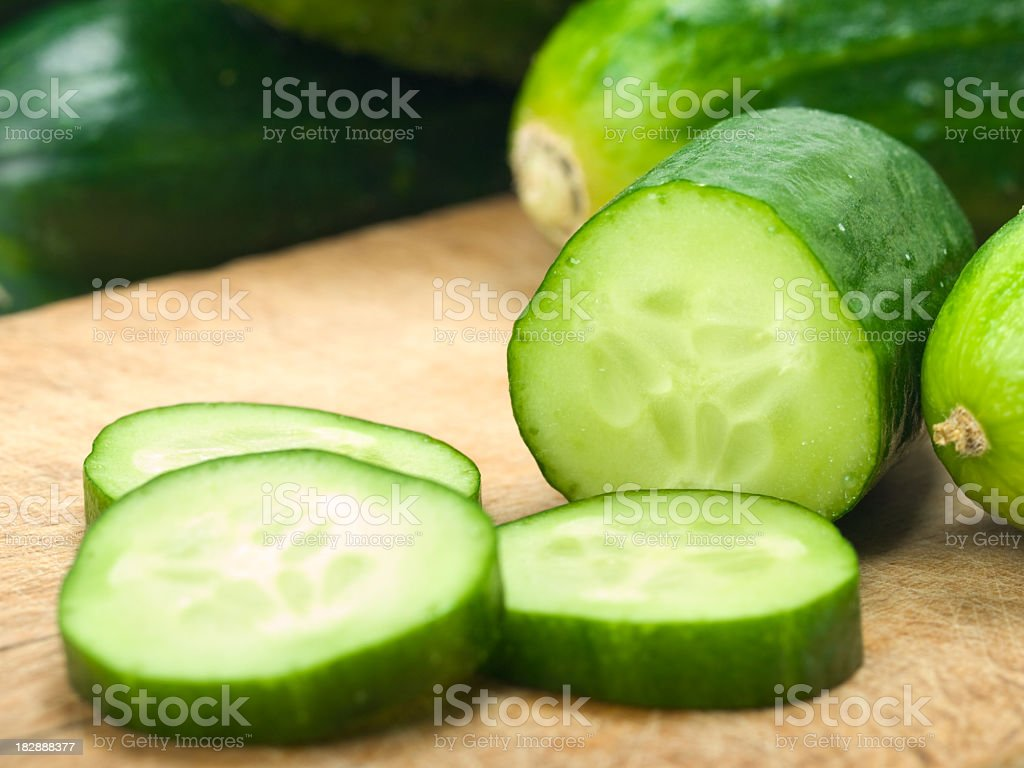Sliced up cucumbers on wooden board stock photo