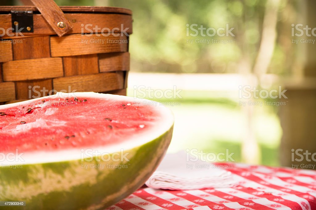 Sliced watermelon outdoors on picnic table. Summer. Basket. stock photo