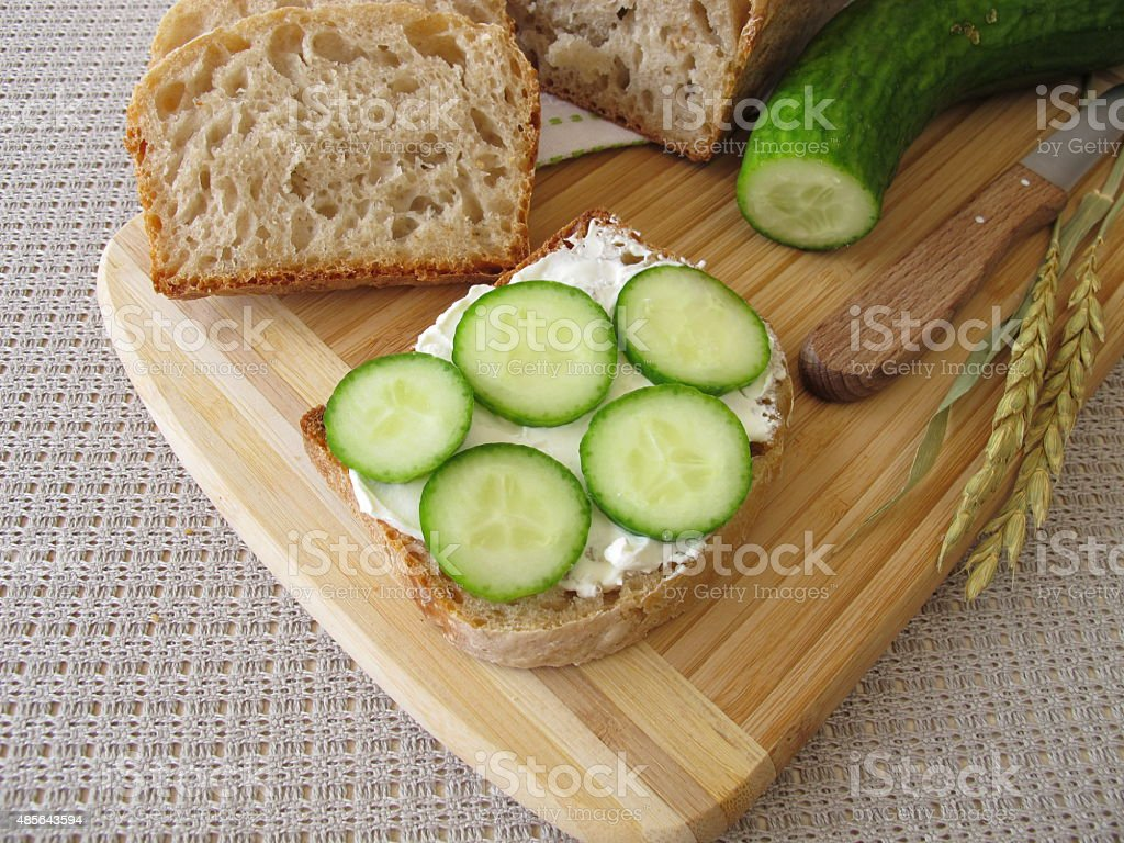 Sliced white bread with cream cheese and cucumber stock photo