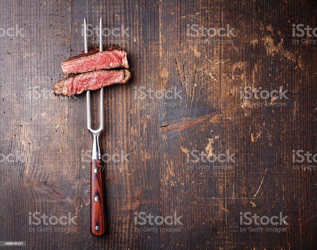 Slices of beef steak on meat fork stock photo