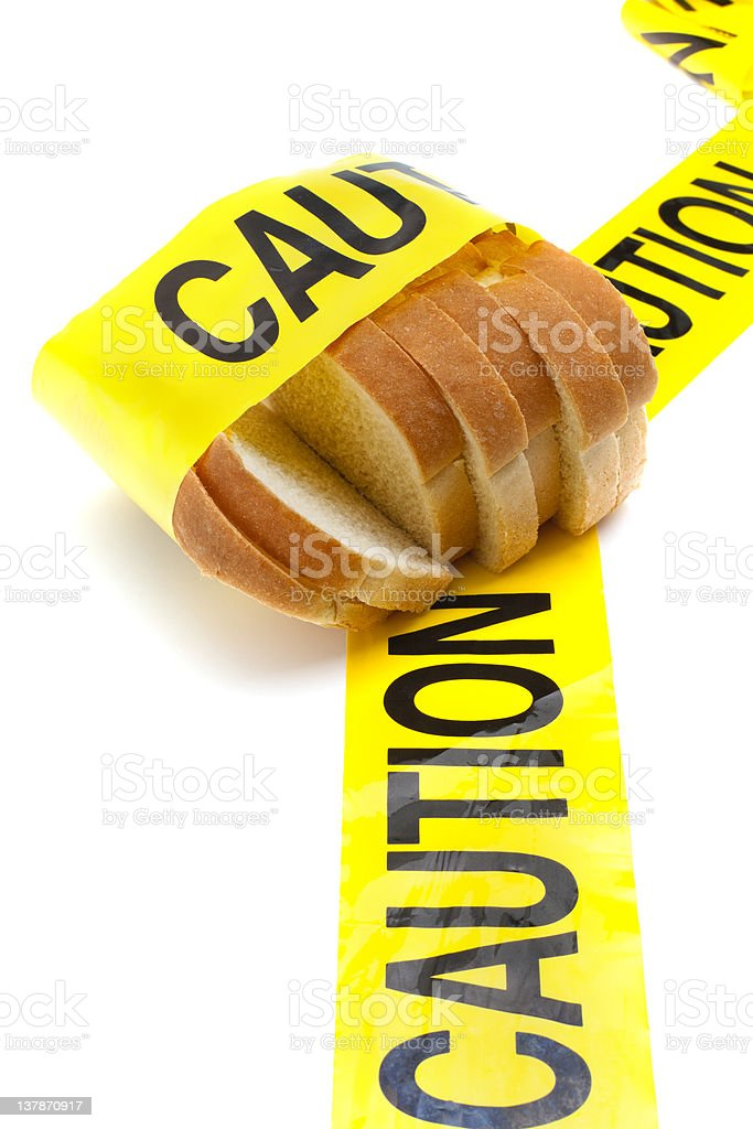 Slices of bread wrapped with yellow caution tape royalty-free stock photo