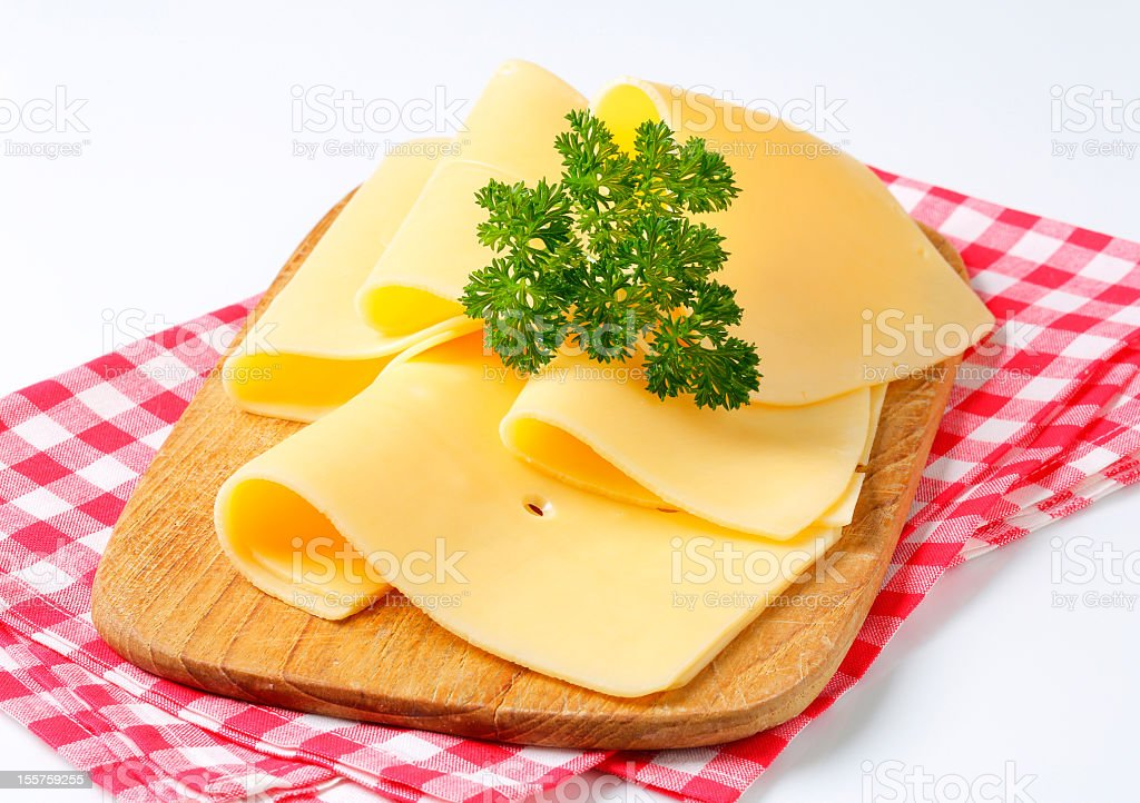 slices of cheese on a cutting board stock photo
