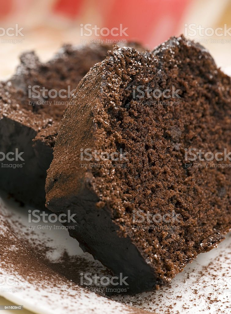 Slices of chocolate cake sprinkled with chocolate powder stock photo