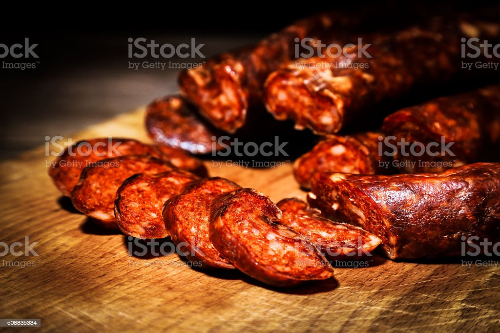 Slices of chorizo sausauge on a cutting board stock photo